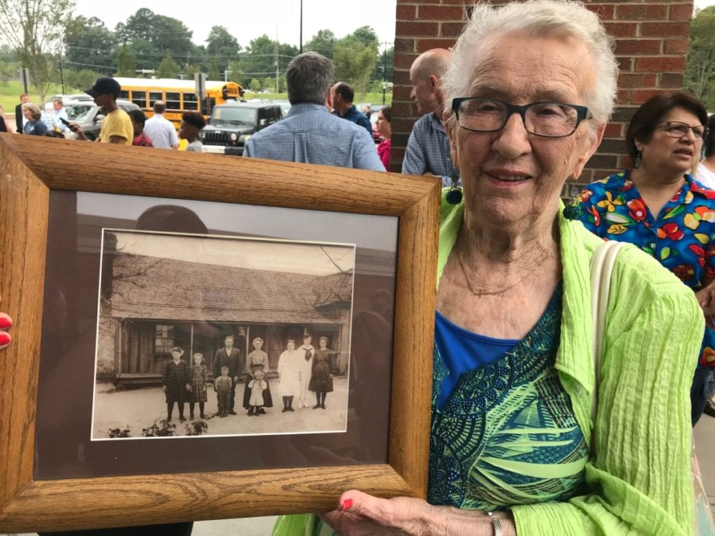 Hill family member Beverly Graham displays a picture of the family and original homestead. Her father is the young boy (center) in overalls. (photo by Rebecca Gaunt)