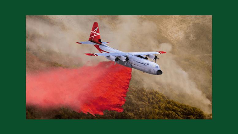 FireHerc firefighting airtanker in flight spreading a bright red flame retardant.