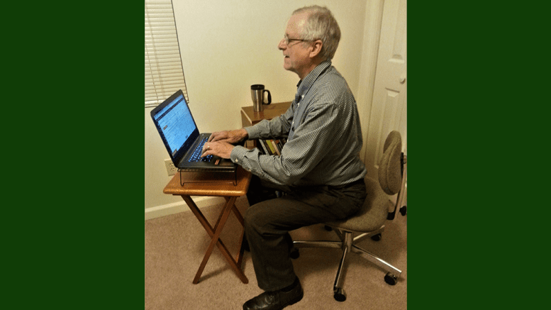 Larry Johnson, the editor and publisher of the Cobb County Courier seated in an office chair in front of a small table with a laptop