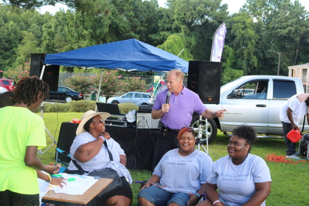 Cobb County Police Chief Michael Register speaks while event organizer Monica Delancy looks on (photo by Larry Felton Johnson)