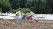 Riverview Landing construction crew at work, crouched over a concrete slab with pipes and conduit