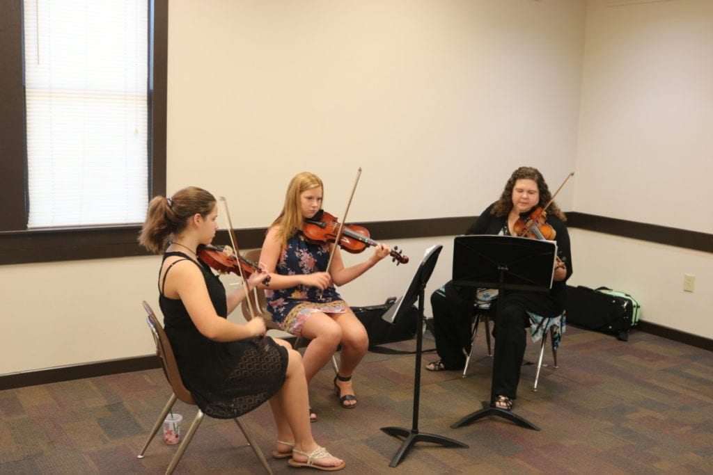 Three women seated playing violins