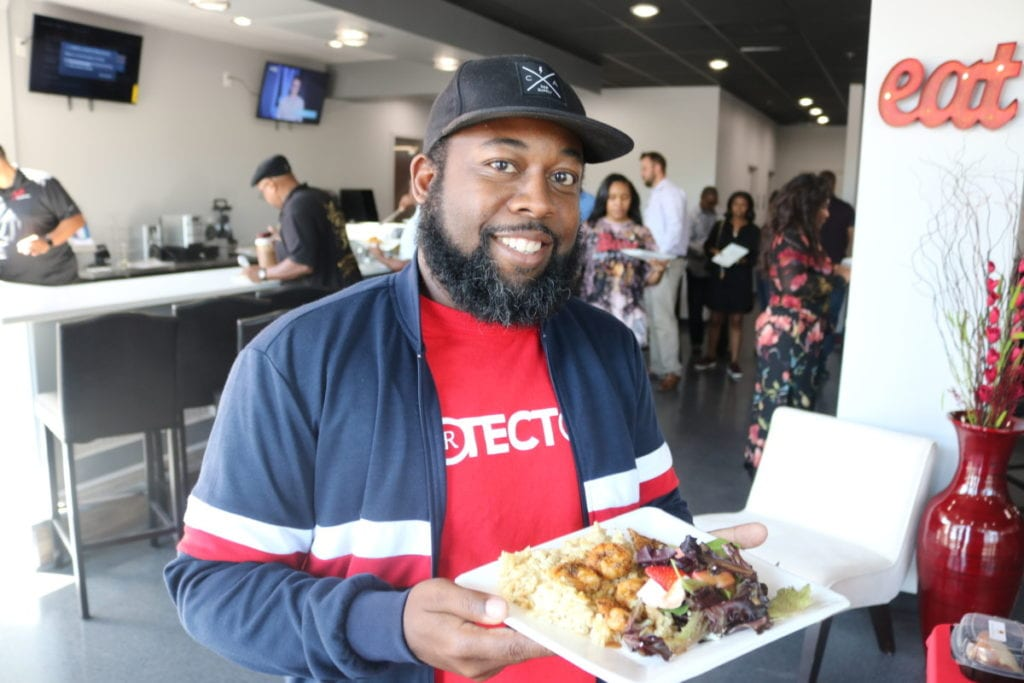 South Cobb Alliance organizer and Cafe Social House customer Tre'Hutchins with a plate of the restaurant's food (photo by Larry Felton Johnson)