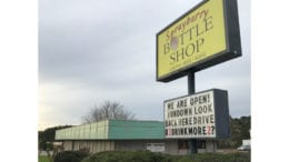 Brij Patel, director of marketing for Sprayberry Bottle Shop, has been vocal with his frustration over the condition of the adjacent Sprayberry Crossing property and the illegal dumping that takes place near his store. He put this sign up in conjunction with the planned social media campaign. (photo by Rebecca Gaunt)
