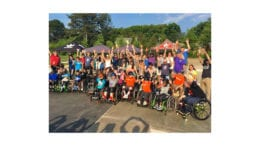 participants in wheelchairs along with supporters at adaptive skateboarding clinic