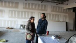 Linda and Ben Brackner in the Green Room, with ongoing work to the unfinished space in the background