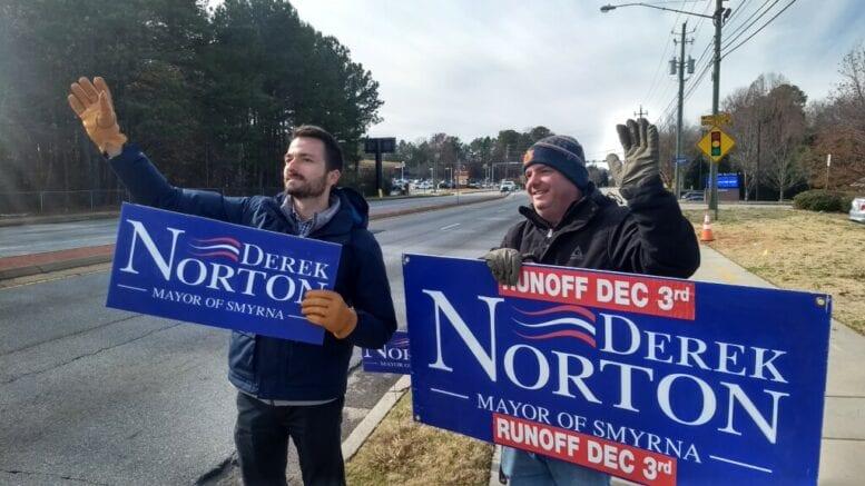 Two men waving Derek Norton signs on Spring Road in article Derek Norton wins