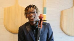 Khalil Payne holding his cello, standing
