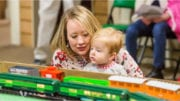 child looks over model railroad at museum